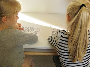 A first and second grader practicing letter and key recognition on a keyboard.